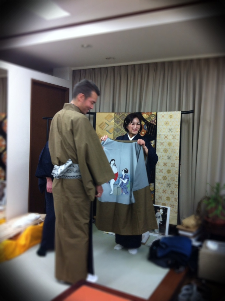 The shop owner holding my Haori (Jacket)